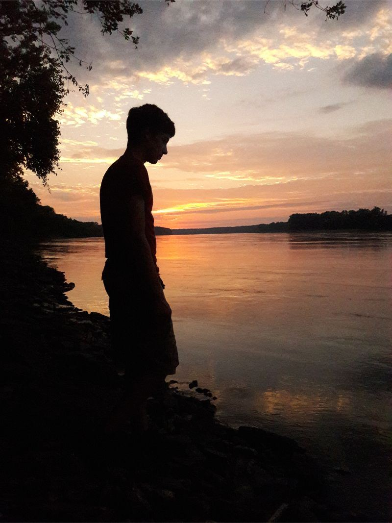 Front Cover - photo of a boy's silhouette in front of the river at sunset